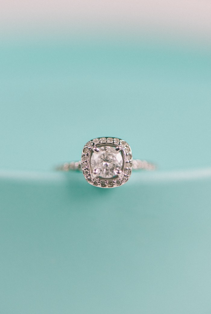 cushion cut halo engagement ring on turquoise