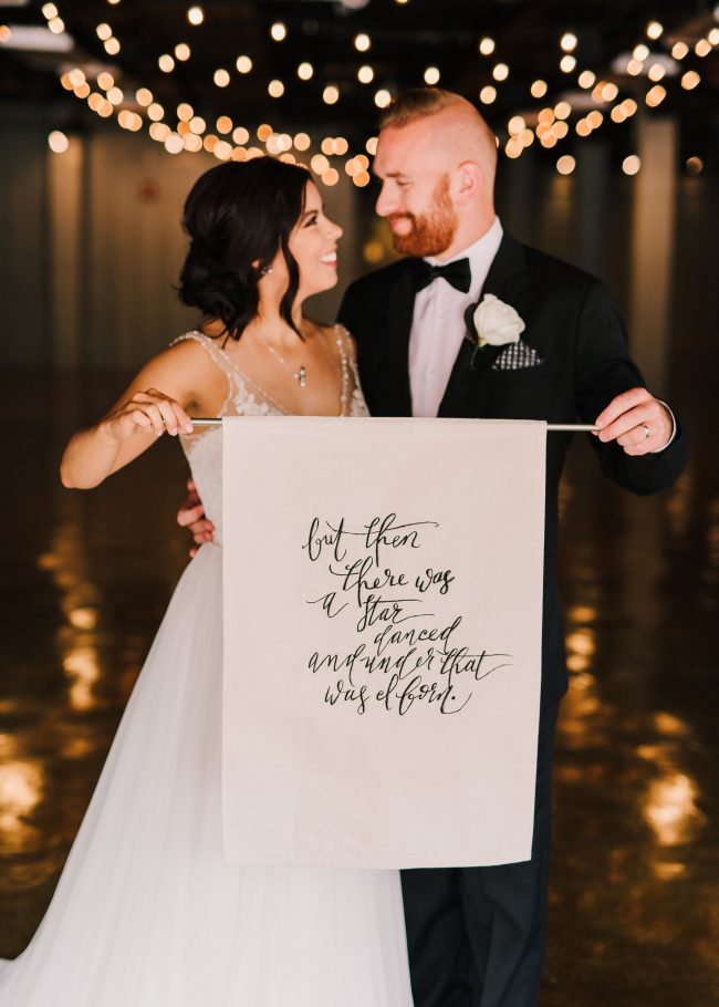 bride and groom full length photo with shakespeare quote sign
