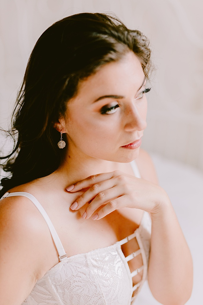 Styled boudoir photo featuring dark haired caucasian model with white lingerie and white druzy earrings made by J'Adorn Designs