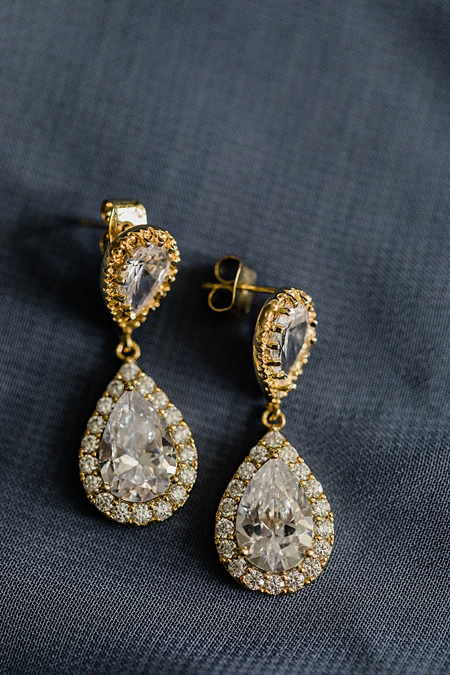 Classic sparkly gold bridal drop earrings on a navy blue background for an Annapolis wedding at Chesapeake Bay Beach Club, featuring jewelry by J'Adorn Designs bridal jeweler