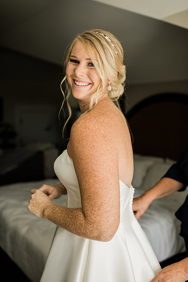 Smiling blonde bride in sparkly gold bridal teardrop earrings by J'Adorn Designs bridal jeweler for a classic Annapolis wedding at Chesapeake Bay Beach Club
