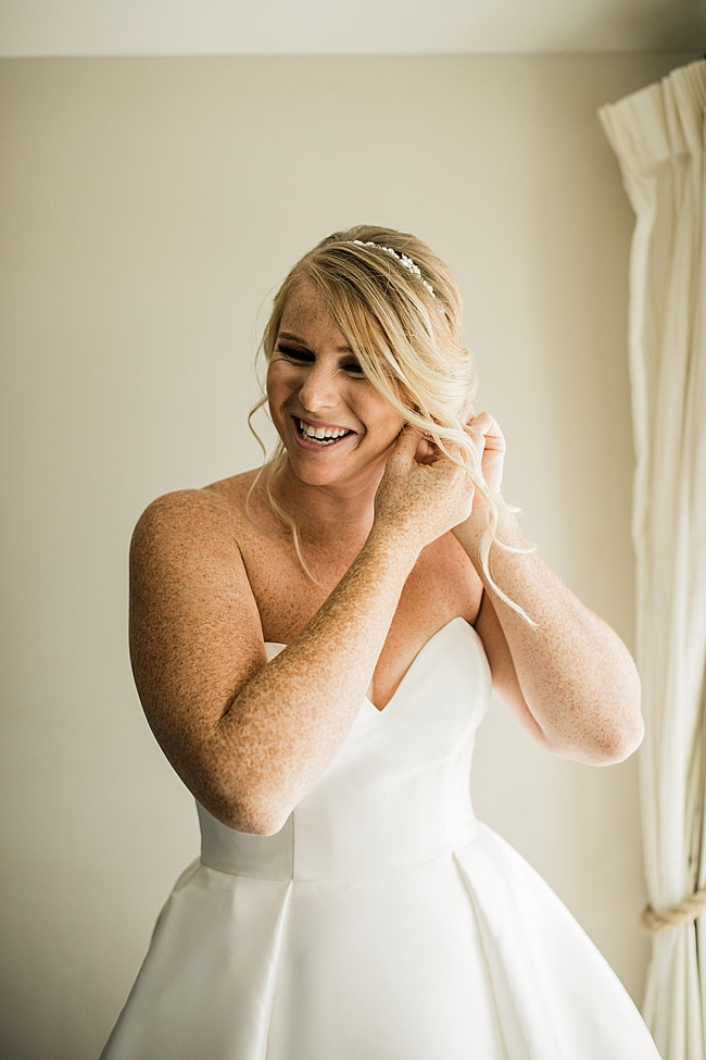 Smiling blonde bride putting on sparkly gold bridal teardrop earrings by J'Adorn Designs bridal jeweler for a classic Annapolis wedding at Chesapeake Bay Beach Club