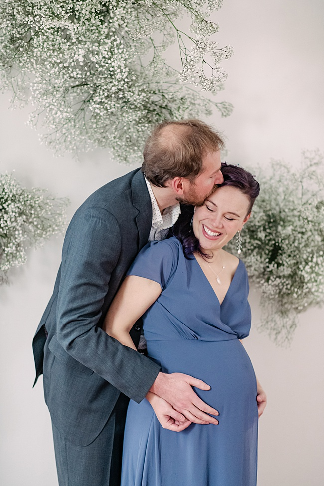 Maternity portrait featuring a smiling couple. The mother-to-be wears a slate grey dress and matching gemstone jewelry