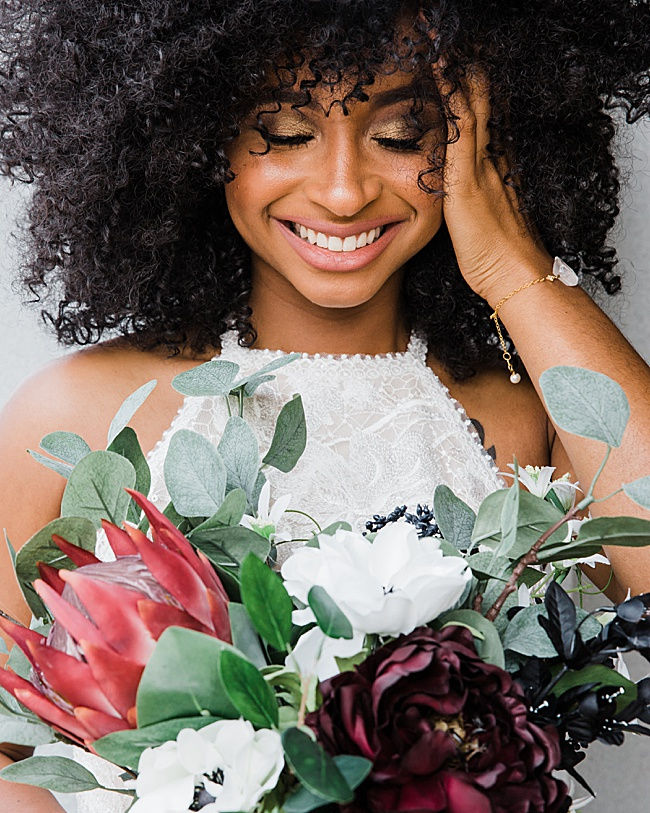 Natural and clean wedding style inspiration featuring an African American bride with curly hair, wearing a white jumpsuit and modern crystal spike bracelet by J'Adorn Designs handcrafted bridal bracelet